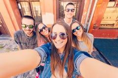Unga vänner som skrattar och tar selfie Royaltyfri Fotografi