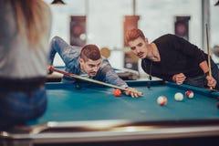 Unga vänner som spelar billiard i kafé Arkivfoto