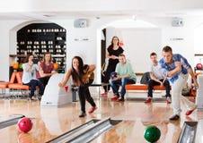 Unga vänner som spelar i bowlingbana Royaltyfri Fotografi