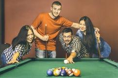 Unga vänner som spelar pölen på salongen för billiardtabell - lyckligt kamratskap fotografering för bildbyråer
