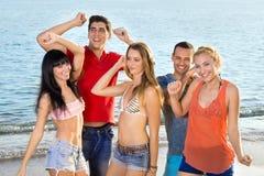 Unga vänner som tycker om på stranden på sommar Fotografering för Bildbyråer