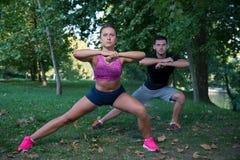 Unga vård- par som gör sträcka övningsatt koppla av och uppvärmning, når att ha joggat och de har kört in, parkerar royaltyfri bild