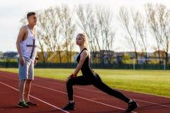 Unga vård- par som gör sträcka att koppla av för övning Arkivbild