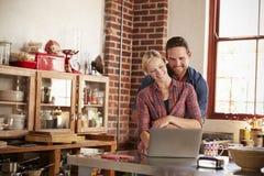 Unga vita par genom att använda bärbara datorn, i att omfamna för kök royaltyfri bild