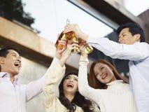 Unga vänner som firar med öl Arkivbild