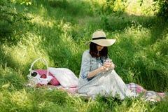 unga vuxen människa Den unga kvinnan i en skog på en picknick ser in i en sm Arkivfoton