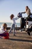 Unga vuxna flickvänner som lastar av bagage från bilen, lodlinje royaltyfri bild