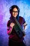 Unga vuxna kvinnor för Nerdgeek som rymmer att spela tangentbordet över den färgrika rosa och blåa neon tända väggen Dobbelgamers arkivfoton