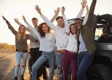 Unga vuxna vänner med händer i luftanseendet med jeepen, slut upp royaltyfri foto
