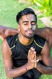 Unga yogamanpraktiker som gör yoga på naturen Asiatisk indisk yogisman på gräset i parkera Bali ö Royaltyfria Bilder