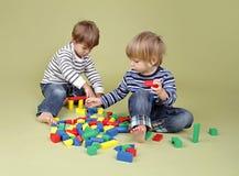 Ungar barn som tillsammans delar och spelar Arkivbilder