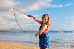Ungar bl?ser bubblan p? stranden bubbles barnet royaltyfri fotografi