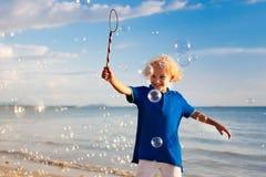 Ungar bl?ser bubblan p? stranden bubbles barnet arkivbilder