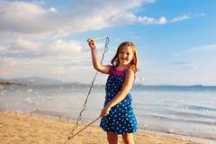 Ungar bl?ser bubblan p? stranden bubbles barnet royaltyfria bilder