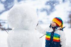 Ungar bygger snögubben Barn i snow körning av rolig pulkavinter arkivbild