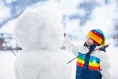 Ungar bygger snögubben Barn i snow körning av rolig pulkavinter arkivfoton