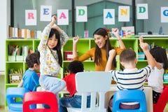Ungar för lycklig asiatisk lärarinna och för blandat lopp i klassrumet, skolabegrepp för dagis pre royaltyfri foto
