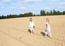 Ungar - flickor som går på fält Royaltyfri Bild