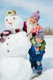 Ungar gör en snögubbe fotografering för bildbyråer