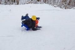 Ungar har gyckel som sledding med snöglidbanor Arkivbilder