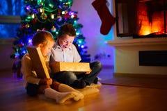 Ungar hemma på gåvor för öppning för julhelgdagsafton Royaltyfria Foton