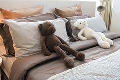 Ungar hyr rum med dockor och kuddar på säng Arkivbilder