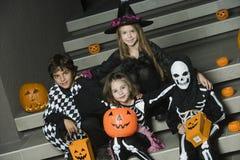 Ungar i allhelgonaafton kostymerar sammanträde på trappa royaltyfria bilder