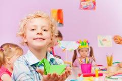 Ungar i dagis gör origami, stående av pojken Royaltyfri Foto