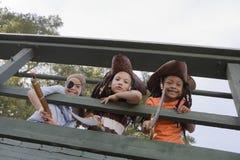 Ungar i dräkter som ser till och med träräcke Arkivbild