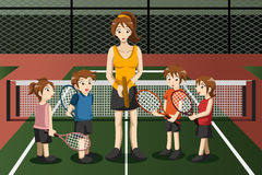 Ungar i en tennisklubba med instruktören Arkivbild