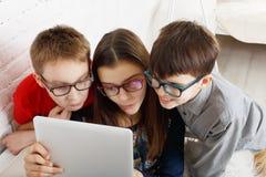 Ungar i exponeringsglas med minnestavlan, datorböjelse Fotografering för Bildbyråer