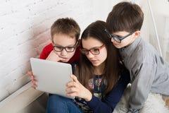 Ungar i exponeringsglas med minnestavlan, datorböjelse Royaltyfri Bild