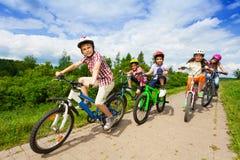 Ungar i hjälmar som tillsammans rider cyklar Arkivbild
