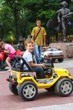 Ungar i lekområdet som rider en leksakbil Nikolaev Ukraina Royaltyfri Bild