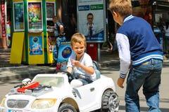 Ungar i lekområdet som rider en leksakbil Nikolaev Ukraina Royaltyfri Fotografi