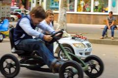 Ungar i lekområdet som rider en leksakbil Nikolaev Ukraina royaltyfria bilder