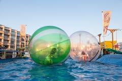 Ungar i såpbubblor som svävar på vattnet Arkivbild