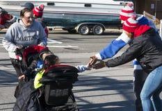 Ungar i sittvagn får höga pickolaflöjter på slutet av en lokal tacksägelse r royaltyfria bilder