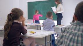 Ungar i skola, barn lyfter deras händer för att svara lärare frågan, skolflicka går till svart tavla att skriva enkelt lager videofilmer
