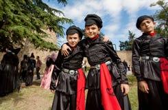 Ungar i traditionella georgiska dräkter som har gyckel tillsammans under av stadsfestival Fotografering för Bildbyråer