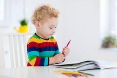 Ungar läser, skriver och målar barn som gör läxa Royaltyfri Foto