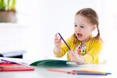 Ungar läser, skriver och målar barn som gör läxa Royaltyfri Bild