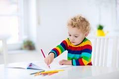 Ungar läser, skriver och målar barn som gör läxa Royaltyfri Fotografi