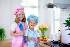 Ungar lagar mat i vitt k?k Laga mat f?r barn royaltyfri fotografi
