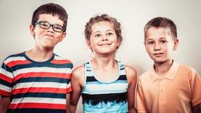 Ungar liten flicka och pojkar som gör enfaldigt framsidauttryck Royaltyfri Fotografi