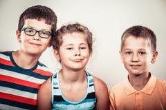 Ungar liten flicka och pojkar som gör enfaldigt framsidauttryck Royaltyfri Foto