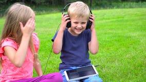 Ungar lyssnar musik på minnestavlan utomhus arkivfilmer