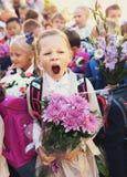 Ungar med blommor på den första skoladagen i Moskva Royaltyfri Foto