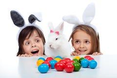 Ungar med den easter kaninen och lotterna av färgrika ägg Arkivfoton