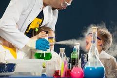 Ungar med den galna professorn som gör vetenskap, experimenterar i laboratoriumet Arkivbild